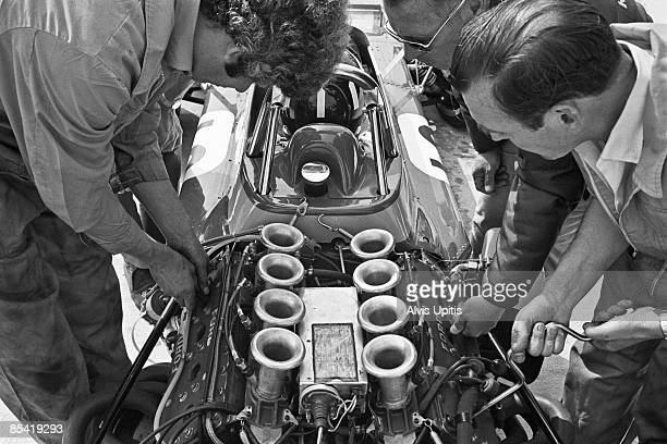Mechanics work on a Cosworth Ford engine in Graham Hill's Brabham BT33 at the Questor Grand Prix in which Formula One cars competed with Formula A...