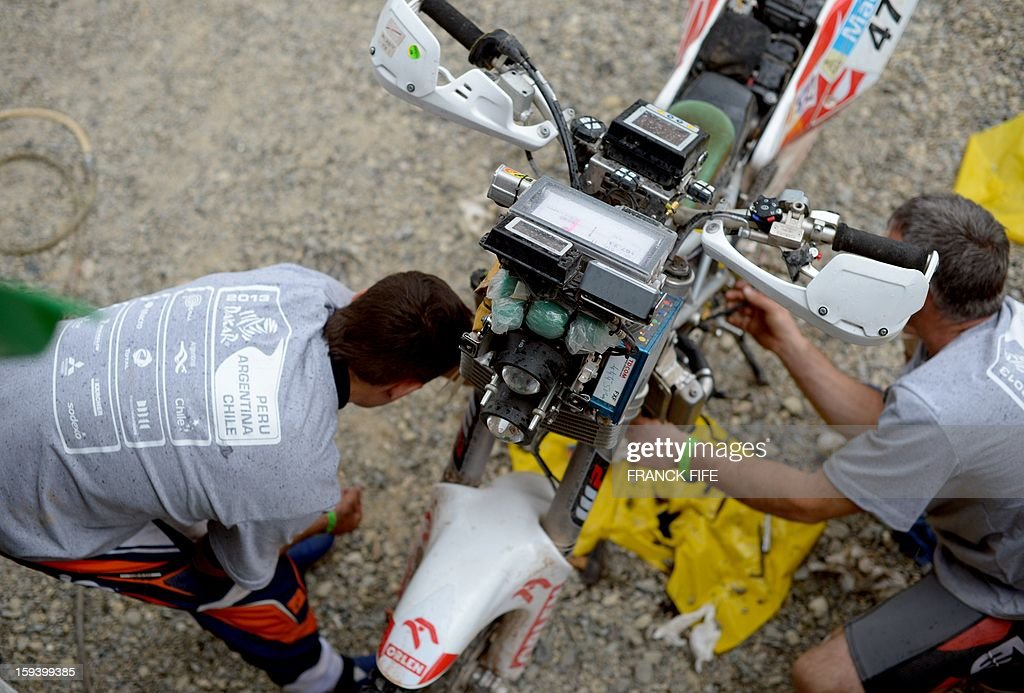 Mechanics work on a motorcycle in Cachi after the Stage 7 of the Dakar Rally 2013 between Calama and Salta, Argentina, on January 11, 2013. The rally takes place in Peru, Argentina and Chile January 5-20. AFP PHOTO / FRANCK FIFE