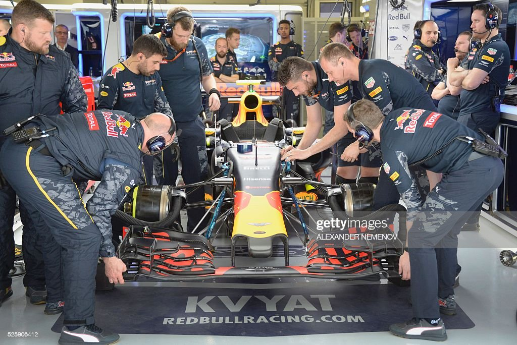 Mechanics work on the car of Red Bull Racing's Russian driver Daniil Kvyat during the first practice session of the Formula One Russian Grand Prix at the Sochi Autodrom circuit on April 29, 2016. / AFP / ALEXANDER