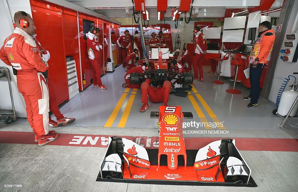 Mechanics work on the car of Scuderia Ferrari's German driver Sebastian Vettel during the first practice session of the Formula One Russian Grand Prix at the Sochi Autodrom circuit on April 29, 2016. / AFP / ALEXANDER
