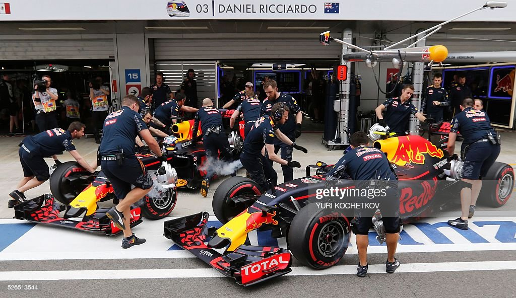 Mechanics work on the cars of Red Bull Racing's Russian driver Daniil Kvyat (front) and Red Bull Racing's Australian driver Daniel Ricciardo during the qualifying session of the Formula One Russian Grand Prix at the Sochi Autodrom circuit on April 30, 2016. / AFP / POOL / YURI