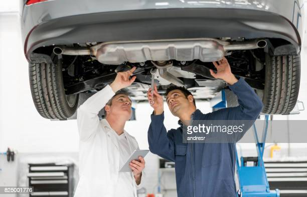 Mechanics working at an auto repair shop checking the chassis of a car