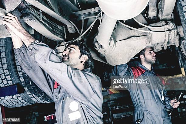 Mecánicos trabajando por debajo de un camión