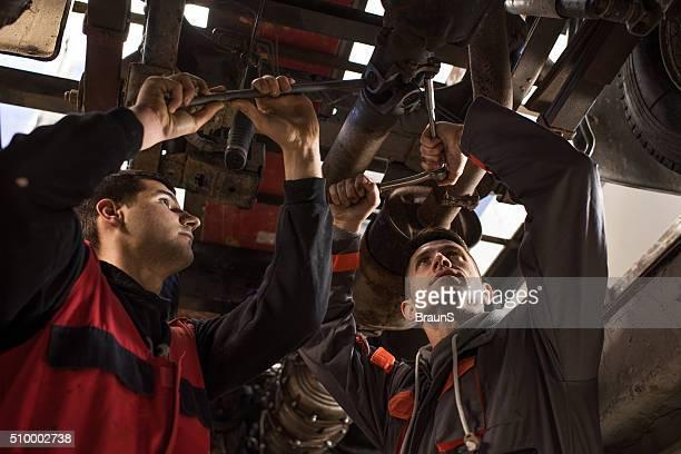 Mechanics working on a bottom part of a car.