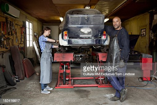 mechanics working on car in garage stock photo getty images. Black Bedroom Furniture Sets. Home Design Ideas