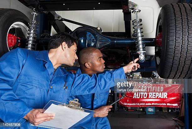 Mechanics working on car shock absorbers