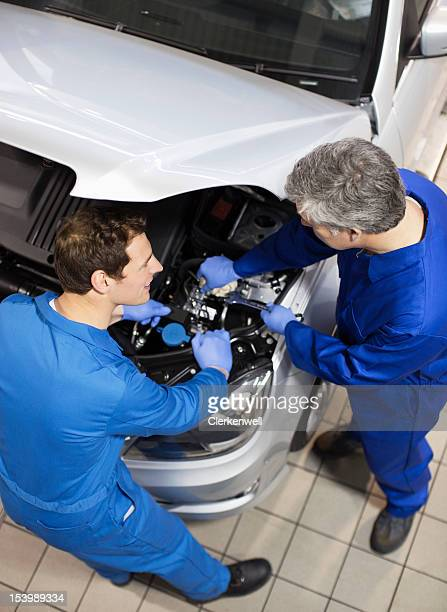 Mechanics working on engine under car hood in auto repair shop