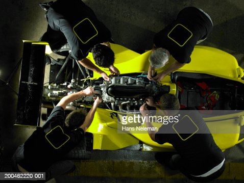 Mechanics working on Formula 1 engine, elevated view : Stock Photo
