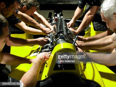 Mechanics working on Formula 1 engine : Stock Photo