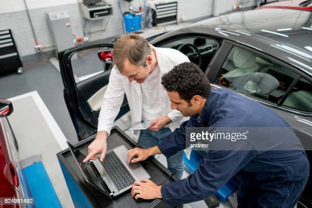 Mechanics working together at an auto repair shop using a computer