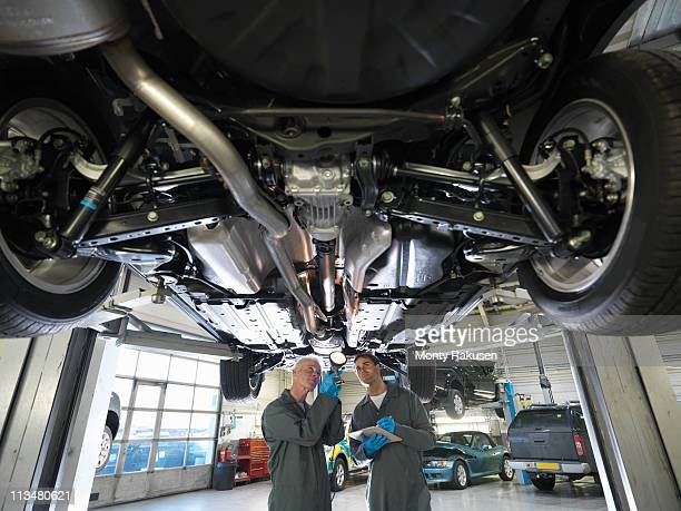 Mechanics working under car in car dealership workshop
