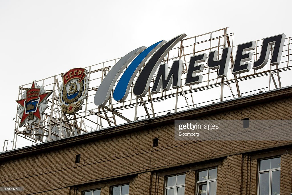 A Mechel logo, right, stands besides old Soviet emblems above administrative offices at OAO Mechel's metallurgical plant in Chelyabinsk, Russia, on Wednesday, July 17, 2013. Mechel, the country's largest producer of coking coal for steelmakers has begun operating its $700m rail production line which can produce 100 meter rails. Photographer: Andrey Rudakov/Bloomberg via Getty Images
