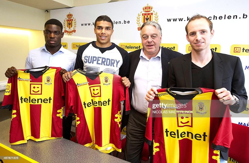 KV Mechelen's new signings Stevy Okitokandjo Jason Adesanya and Tim Matthys pose next to Mechelen's chairman Johan Timmermans with their new shirts...