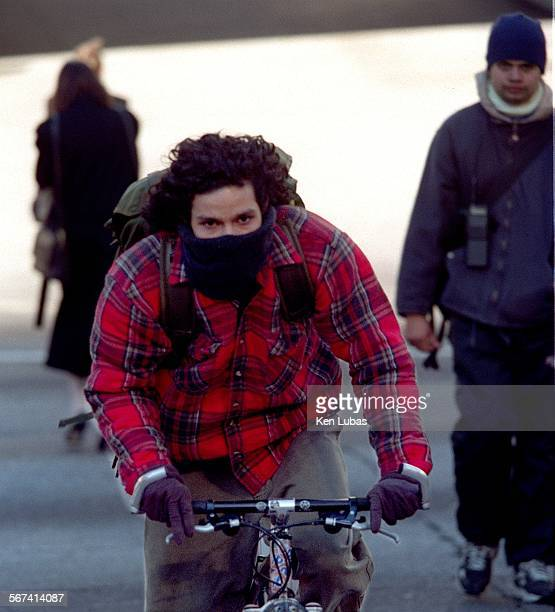 MEcold1kl12/9/97––LOS ANGELES––Bicycle mesenger George Saz crosses Flower Street at Fifth Street in downtown Los Angeles Tuesday bundled up against...
