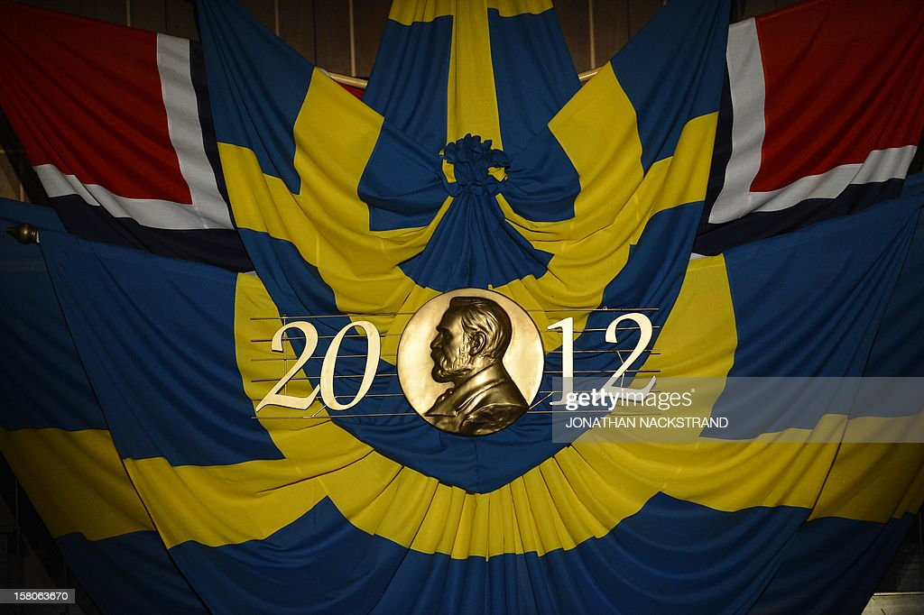 A medal of Alfred Nobel and Swedish flags are seen prior to the Nobel prize awarding ceremony at the Stockholm Concert Hall on December 10, 2012 in Stockholm, Sweden. The winners of the Nobel Prize 2012 in the categories of medicine, physics, chemistry, literature and economics receive their awards from the hands of Sweden's King Carl XVI Gustaf at a formal ceremony, followed by a gala banquet.