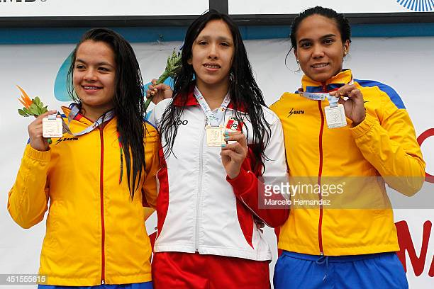 Medal winners Andres Cedron of Peru Cindy Mejia of Colombia and Yenny Tellez of Colombia pose for pictures on the podium after competing in 100 mts...