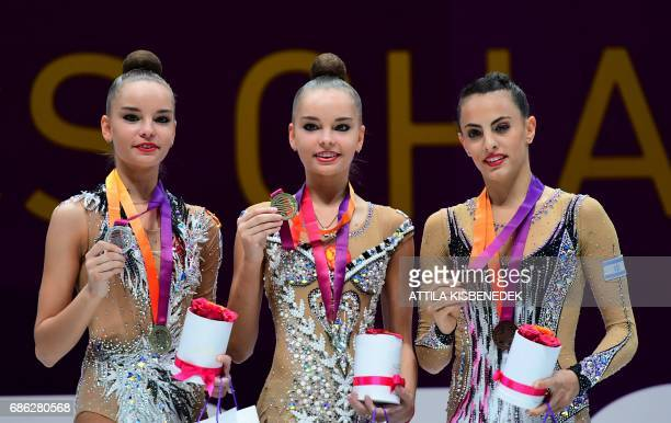 CORRECTION Medalists Russia's Dina Averina of silver Russia's Arina Averina of gold and Israel's Linoy Ashram of bronze celebrate on podium in Papp...