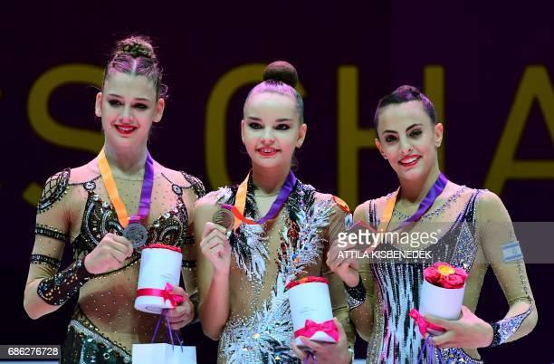Medalists silver winner Russia's Aleksandra Soldatova gold winner Russia's Dina Averina and bronze winner Israel's Linoy Ashram celebrate on podium...