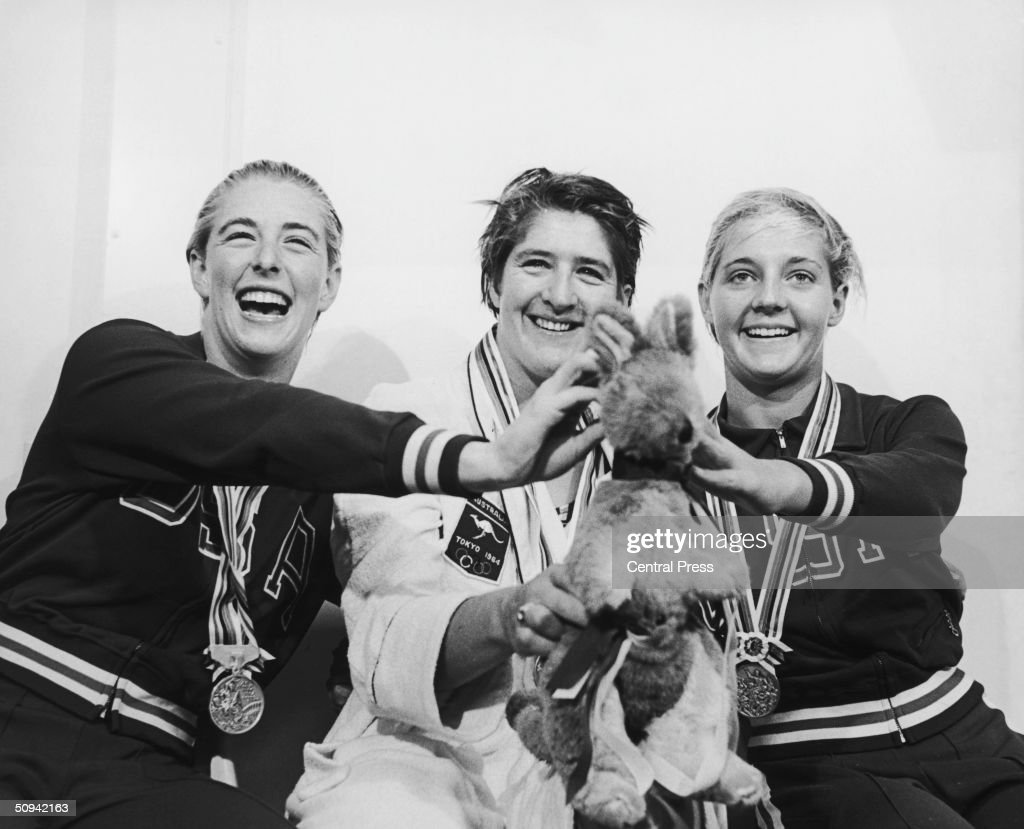 Medallists in the 100 metres freestyle swimming event at the Tokyo Olympics, 15th October 1964. Left to right: silver medallist Sharon Stouder of the U.S.A., third time gold medallist Dawn Fraser of Australia and bronze medallist Kathleen Ellis, also of the U.S.A. Fraser is holding up her lucky kangaroo mascot.
