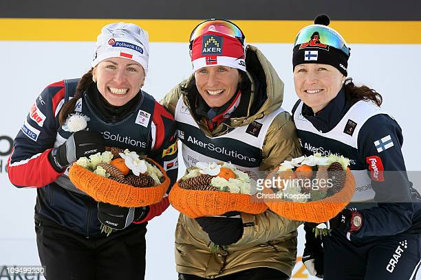 Medallists Justyna Kowalczyk of Poland Marit Bjoergen of Norway and Aino Kaisa Saarinen of Finland celebrate following the Ladies Cross Country 10km...