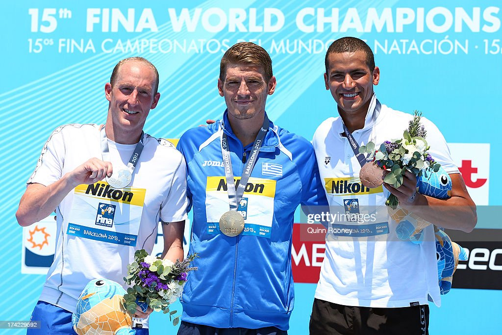 Medallists Thomas Peter Lurz of Germany (silver), Spyridon Gianniotis of Greece (gold) and <a gi-track='captionPersonalityLinkClicked' href=/galleries/search?phrase=Oussama+Mellouli&family=editorial&specificpeople=2297983 ng-click='$event.stopPropagation()'>Oussama Mellouli</a> of Tunisia (bronze) celebrate on the podium after the Open Water Swimming Men's 10k race on day three of the 15th FINA World Championships at Moll de la Fusta on July 22, 2013 in Barcelona, Spain.