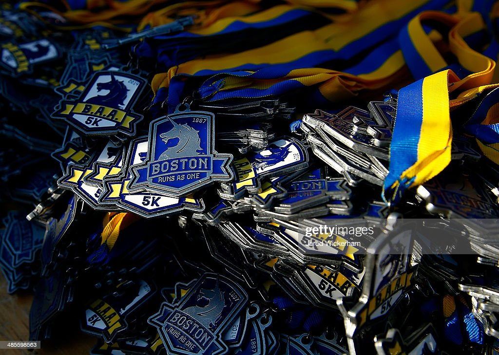 A. 5K medals that read, 'Boston Run As One', are displayed on a table near the finish line of the race in the Boston Common on April 19, 2014 in Boston, Massachusetts.