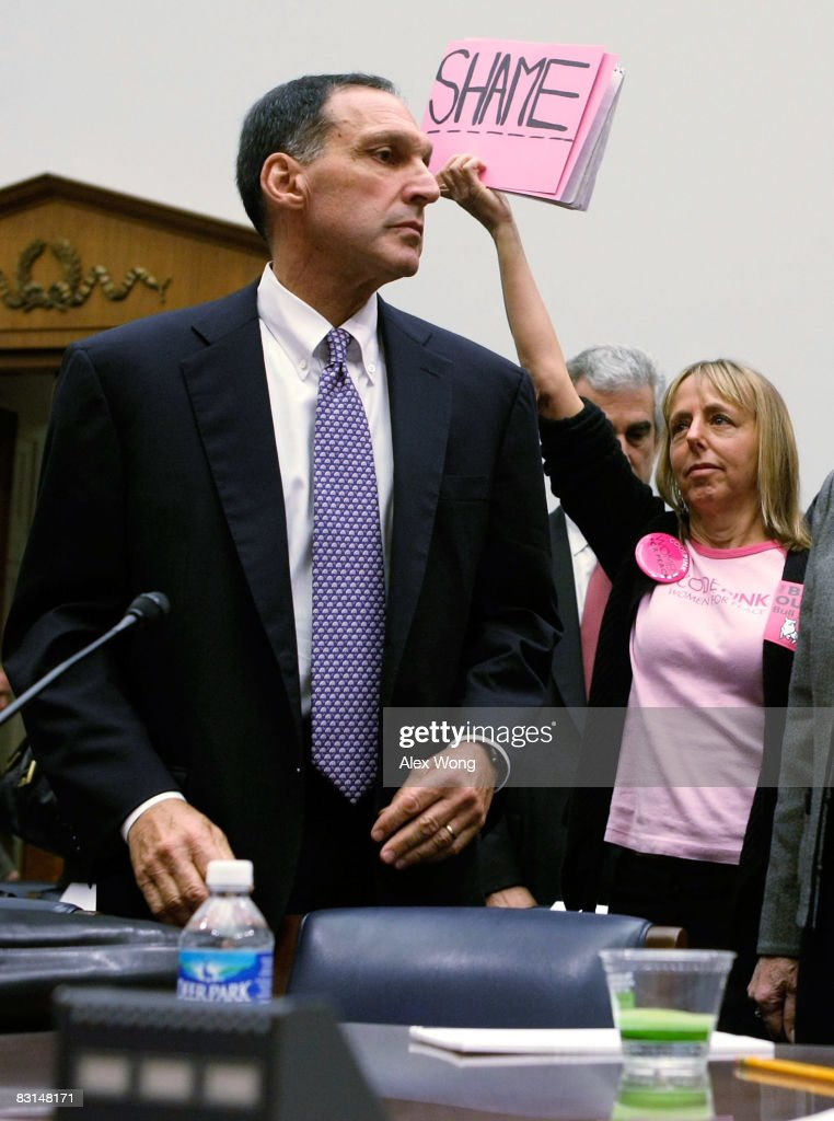 Medea Benjamin of Code Pink protests as Chairman and CEO of Lehman Brothers Richard Fuld Jr takes his seat prior to a hearing before the House...