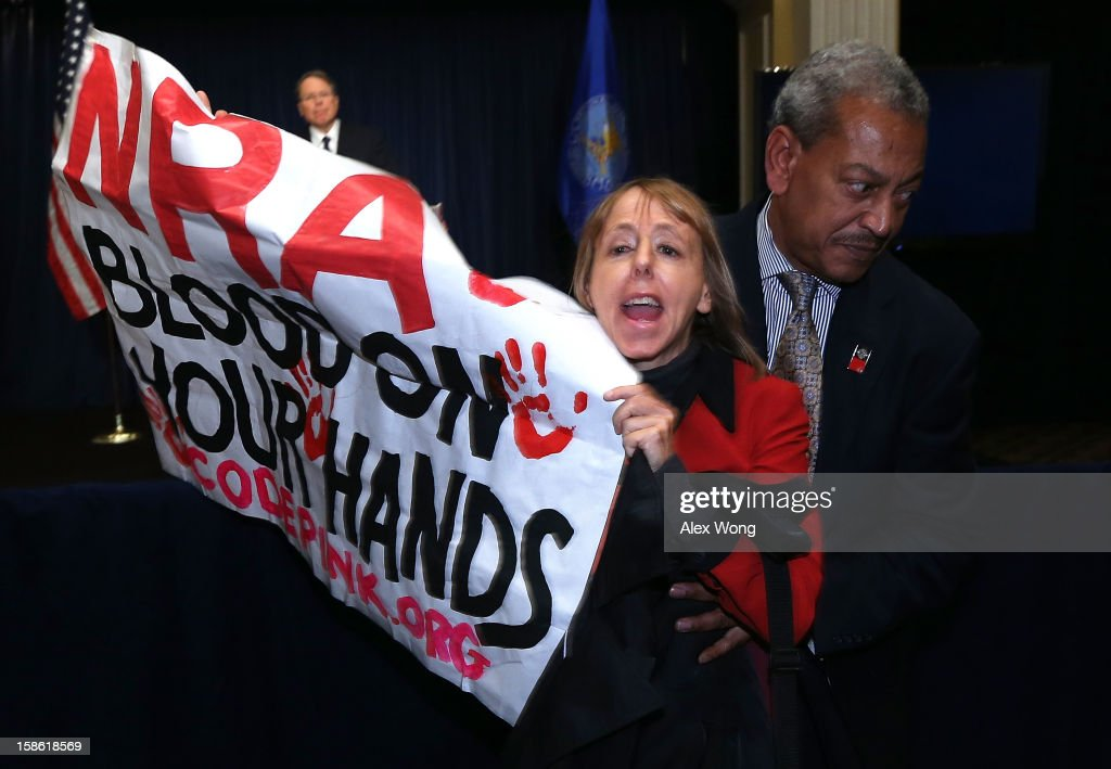 Medea Benjamin of CodePink is removed by a secretary personnel as she protests during NRA CEO and Executive Vice President Wayne LaPierre's news...