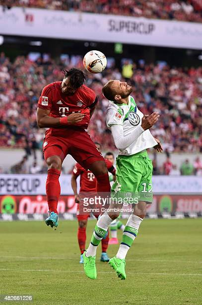 Medhi Benatia of FC Bayern Muenchen and Bas Dost of VfL Wolfsburg go up for a header during the DFL Supercup 2015 match between VfL Wolfsburg and FC...