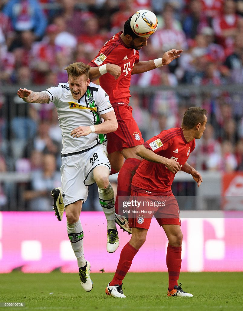 Medhi Benatia of Muenchen jumps for a header with Andre Hahn of Gladbach during the Bundesliga match between FC Bayern Muenchen and Borussia Moenchengladbach at Allianz Arena on April 30, 2016 in Munich, Germany.