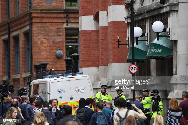 Media and onlookers gather as Police guard the entrance to Granby House in the city centre following an armed raid on May 24 2017 in Manchester...