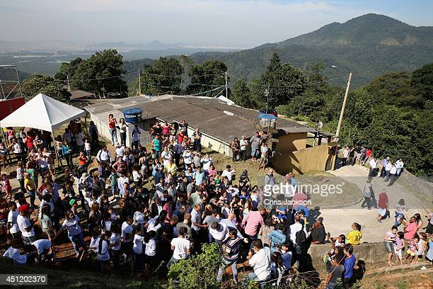 Media and villagers gather around Prince Harry as he visits Cota 200 a small village in the Brazilian Atlantic Rainforest on June 25 2014 in Cota 200...