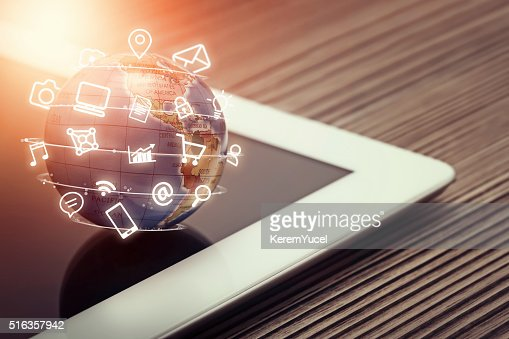 media app icons flying around globe on tablet computer : Stock Photo