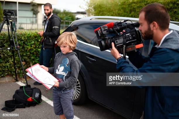 A media cameraman films a sketch of Brazilian superstar Neymar made by a boy as they wait for Neymar's arrival from Barcelona outside the business...