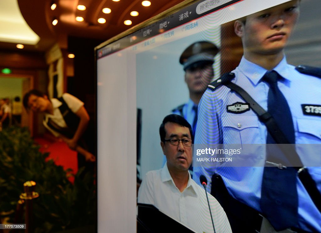 A media center television shows an image of former police chief Wang Lijun as he gives evidence on the third day of the trial of disgraced politician Bo Xilai at the Intermediate People's Court in Jinan, Shandong Province on August 24, 2013. Once one of China's highest-flying politicians, Bo Xilai found himself in the criminal dock on trial for bribery and abuse of power in the country's highest-profile prosecution in decades. AFP PHOTO/Mark RALSTON