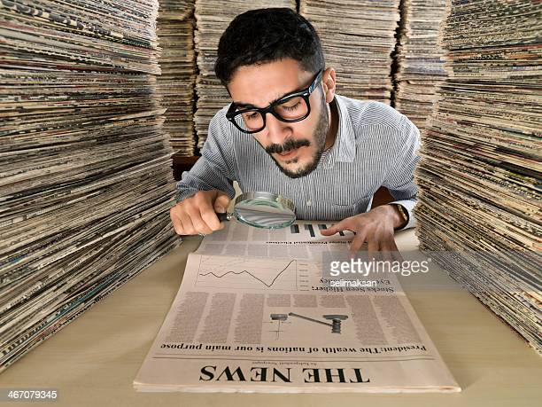 Media consultant looking at newspaper through magnifying glasses