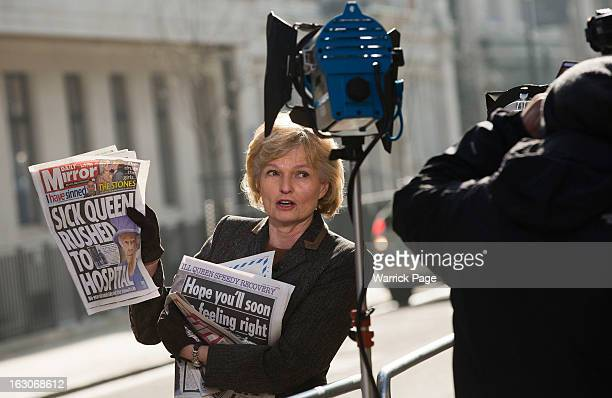 A media correspondent displays the front page of a British newspaper outside the King Edward VII Hospital where Queen Elizabeth II has been admitted...