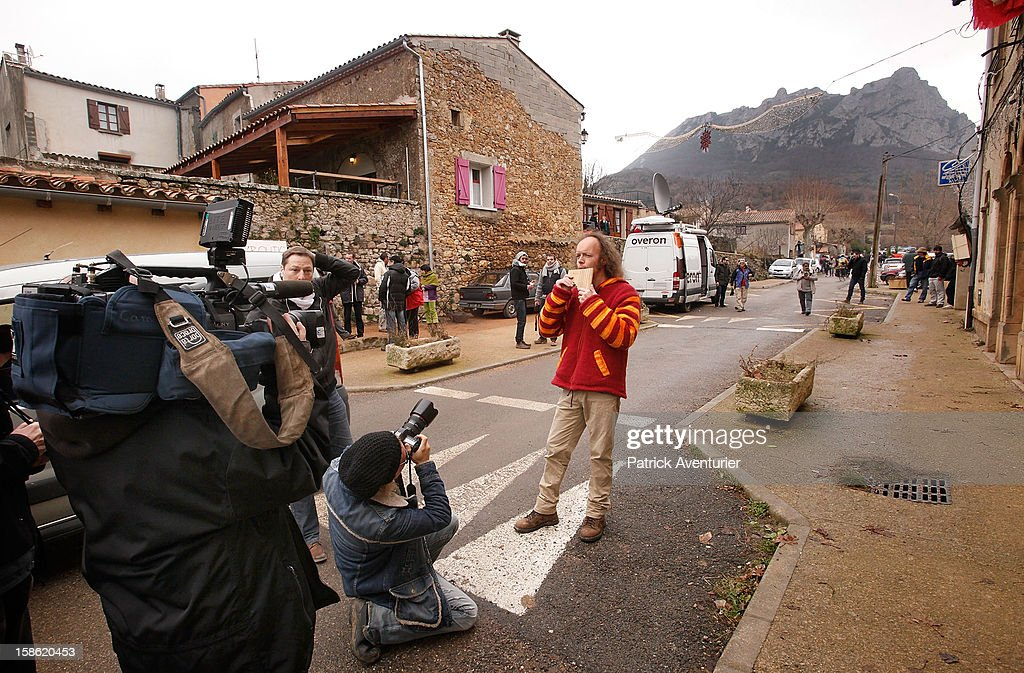 Media film and photograph Sylvain Durif, aka Durif Oriana, who claims to embody 'the energy of the Cosmic Christ announced by Nostradamus' as he playes pan pipes in Bugarach village on December 21, 2012 in Bugarach, France. The prophecy of an ancient Mayan calendar claimed that today would see the end of the world, and that Burgarach is the only place on Earth which will be saved from the apocalypse.