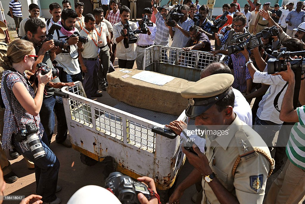 Media gather around the coffin carrying the body of India-born nurse Jacintha Saldanha, 46, after she was brought out of the Bajpe Airport in Mangalore on December 16, 2012. The body of Saldanha who was found hanged after taking a hoax call to the hospital treating Prince William's wife arrived in Mangalore following a memorial mass in London. AFP PHOTO/ Manjunath KIRAN