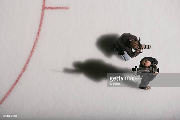 Media members stand on the ice during the NHL game between the New Jersey Devils and the New York Islanders on February 17 2007 at the Nassau...