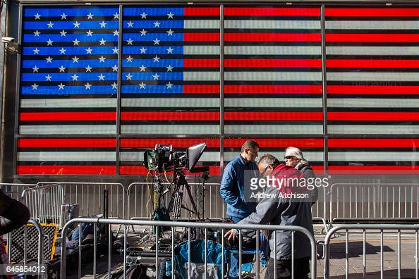 Media people setting up camera equipment in a designated area ring fences with crowd control barriers in front of a large digital Flag of the United...