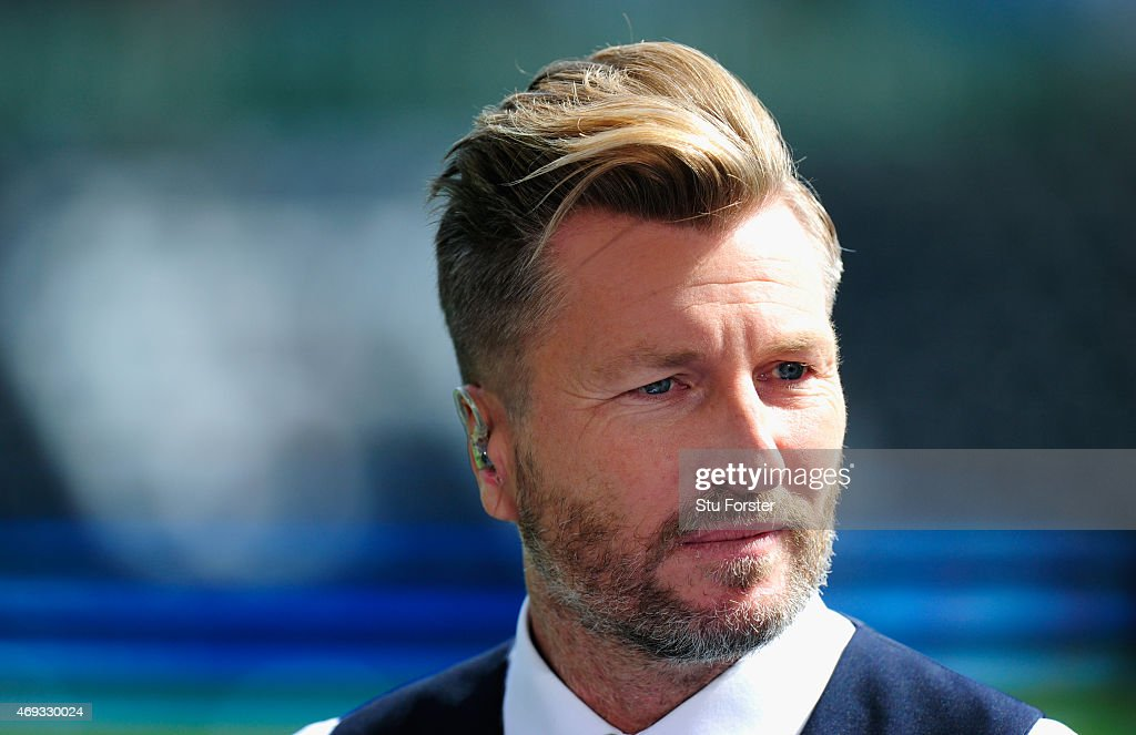 Media pundit Robbie Savage looks on before the Barclays Premier League match between Swansea City and Everton at Liberty Stadium on April 11 2015 in...