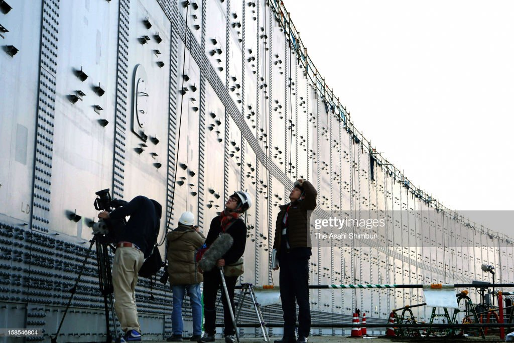Media reporters look up the 18-meter-high breakwater in preparation for possible huge earthquake and tsunami, at Chubu Electric Power Co Hamaoka Nuclear Power Plant on December 18, 2012 in Omaezaki, Shizuoka, Japan. The wall is under construction across the 1.6 kilometers coast line of the premise, will be completed in March 2013.