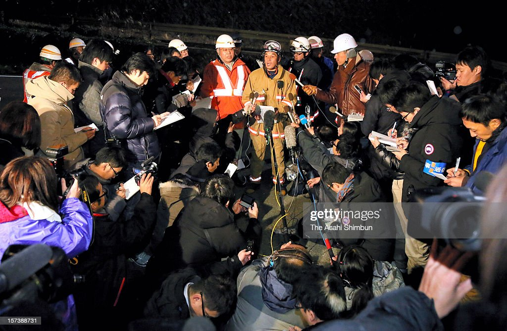 Media reporters surround a head of firefighters during a media briefing outside Sasago Tunnel of the Chuo expressway on December 2, 2012 in Otsuki, Yamanashi, Japan. The concrete ceiling panels of the tunnel collapsed more than 110 metres and at least 9 people confirmed dead.
