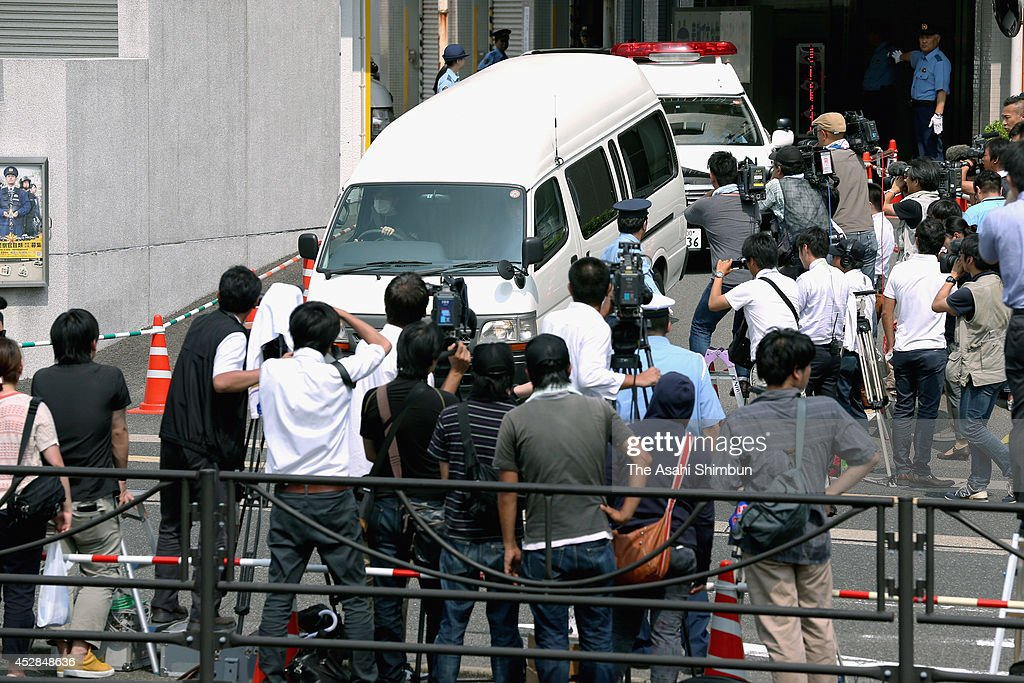 Media reporters surround a police car carrying the girl killed her classmate to the prosecutor's office at a police station on July 28 2014 in Sasebo...