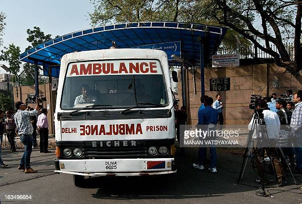 Media representatives surround an ambulance as it leaves the main entrance of Tihar Jail in New Delhi on March 11 2013 The main accused in the fatal...