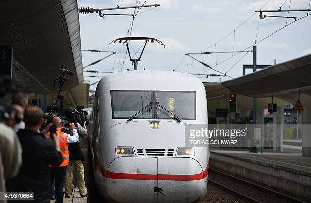 Media representatives watch as an Intercity Express train with Wolfsburg's players and the German Cup DFB trophy arrives at the main station in...