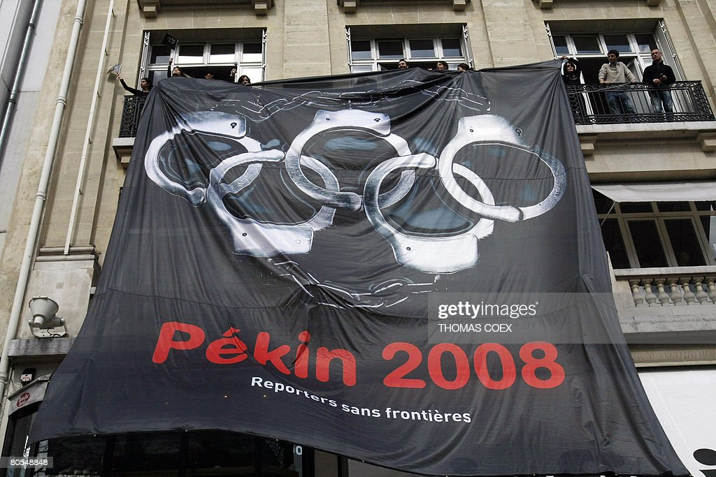 RSF Media rights activists (Reporters without Borders) display a giant banner with the five Olympic rings turned into handcuffs on the Champs Elyses during the Beijing Olympic flame's tour of Paris. Chaotic protests along the path of the flame forced torchbearers to twice interrupt its 28-kilometre (18-mile) route from the Eiffel Tower around the south of Paris, and to place the torch on a bus for safety.