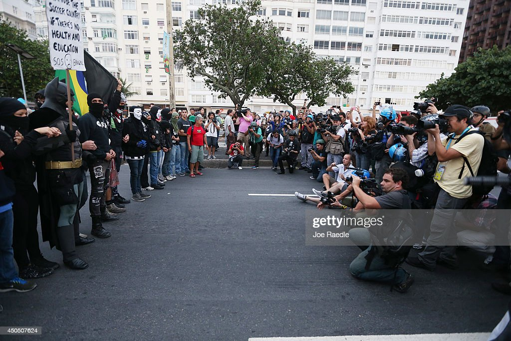 Media shoots protestors linking arms during an anti-World Cup demonstration in the Copacabana section on June 12, 2014 in Rio de Janeiro, Brazil. This is the first day of World Cup play.