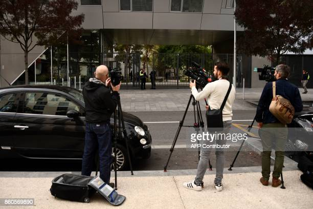 Media stand in front of the BEIN's Paris offices in BoulogneBillancourt near Paris on October 12 during a raid by French authorities following a...